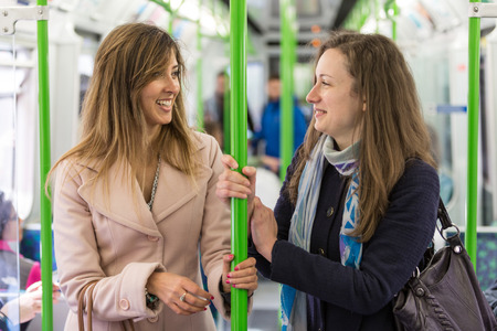 late twenties: Two women commuting with tube in London. They are in their late twenties, both with long hair, looking each other and smiling.