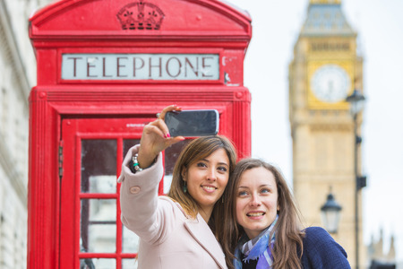 big women: Two beautiful women taking a selfie in London with Big Ben and red phone booth . They are in their twenties, holding the phone and looking at it. Focus on the face.