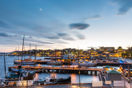 Oslo harbor with boats and yachts at twilight. There are both private and touristic boats, and on some modern buildings.