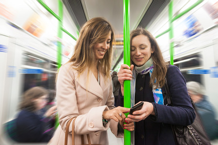 Two women commuting with tube in London. They are in their late twenties, both with long hair. They are looking at smart phone and holding at pole.