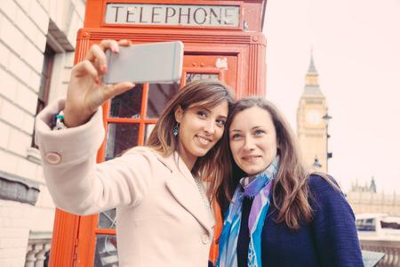 cabina telefono: Dos hermosas mujeres que toman un selfie en Londres con el Big Ben y la cabina de teléfono rojo. Ellos están en sus veintes, sosteniendo el teléfono y mirando a ella. Centrarse en la cara.