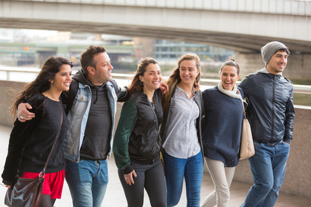 Group of friends walking and having fun together in London. They are four girls and two boys in their twenties, friendship and lifestyle concepts, autumn clothing photo