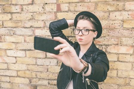 estilo urbano: Mujer inconformista tomar un selfie contra una pared de ladrillo en Londres. Ella lleva la chaqueta de cuero negro y un sombrero. Ella tambi�n lleva gafas y tiene piercings en el cuerpo.