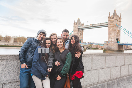 london people: Group of friends taking a selfie using a selfie stick in London with Tower Bridge on background. They are four girls and two boys in their twenties, embracing and having fun together. Stock Photo