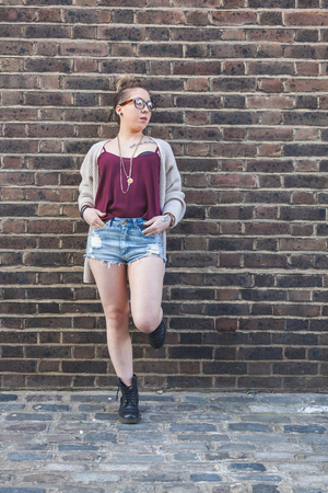 red cardigan: Hipster woman portrait against a brick wall in London. Shes wearing high waisted shorts, a red top and a gray cardigan. She also wears eyeglasses and she has piercings and tattoos Stock Photo
