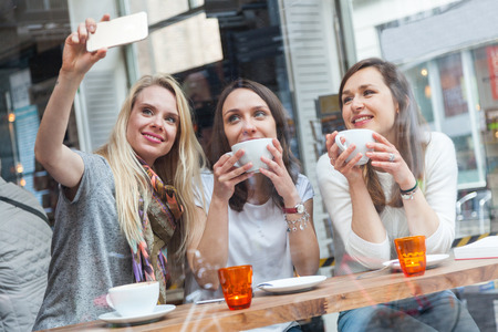 three people only: Happy women taking a selfie in a cafe in Copenhagen. They are in their twenties, enjoying a cup of coffee or tea and wearing smart casual clothes.
