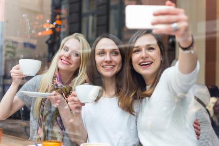 three persons only: Happy women taking a selfie in a cafe in Copenhagen. They are in their twenties, enjoying a cup of coffee or tea and wearing smart casual clothes.
