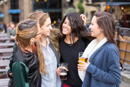 Group of women enjoying a beer at pub in London. They are embraced and laughing. Outdoor scene, winter season, friendship concept. photo