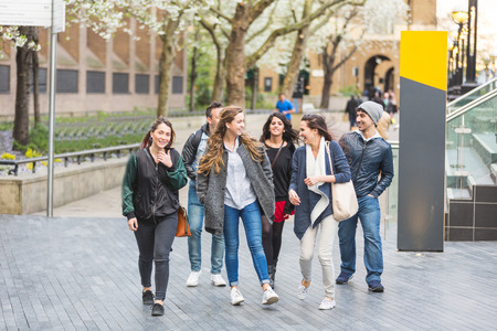 male friends: Group of friends walking and having fun together in London. They are four girls and two boys in their twenties, friendship and lifestyle concepts, autumn clothing
