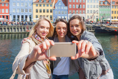 three persons only: Group of women taking a selfie in Copenhagen with colourful houses on background in Nyhavn district. They are in their twenties and they are wearing smart casual clothes.
