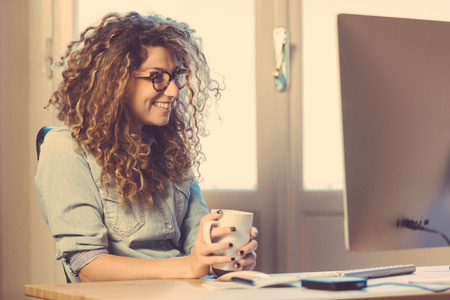 Young woman working at home or in a small office, vintage hipster clothing, curly hair. Cup of tea or coffee on the desk with some technological devices.