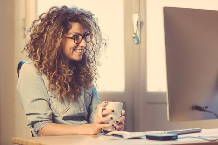 trabajando: Mujer joven que trabaja en casa o en una pequeña oficina, ropa inconformista vintage, pelo rizado. Taza de té o café en la mesa con algunos dispositivos tecnológicos. Foto de archivo