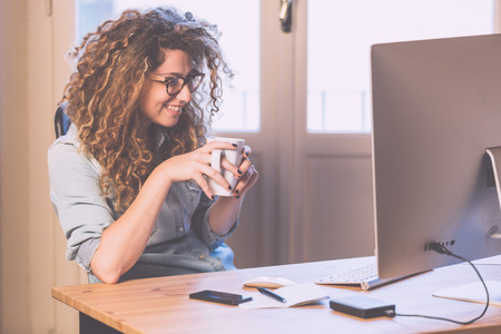 home office interior: Young woman working at home or in a small office, vintage hipster clothing, curly hair. Cup of tea or coffee on the desk with some technological devices.