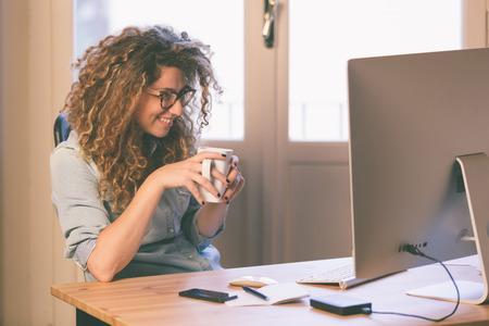 operarios trabajando: Mujer joven que trabaja en casa o en una pequeña oficina, ropa inconformista vintage, pelo rizado. Taza de té o café en la mesa con algunos dispositivos tecnológicos. Foto de archivo