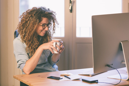 sitting small: Young woman working at home or in a small office, vintage hipster clothing, curly hair. Cup of tea or coffee on the desk with some technological devices.