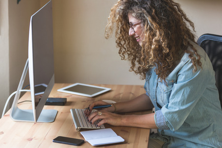 sitting small: Young woman working at home or in a small office, vintage hipster clothing, curly hair. On the wooden desk there are a computer, a digital tablet, a smart phone and a notepad.