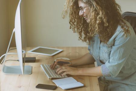typing: Mujer joven que trabaja en casa o en una pequeña oficina, ropa inconformista vintage, pelo rizado. En el escritorio de madera hay un ordenador, una tableta digital, un teléfono inteligente y un bloc de notas.
