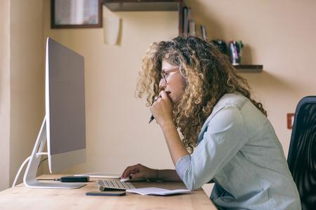 mujer sentada: Mujer joven que trabaja en casa o en una pequeña oficina, ropa inconformista vintage, pelo rizado. En el escritorio de madera hay un ordenador, una tableta digital, un teléfono inteligente y un bloc de notas.