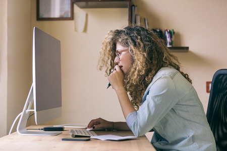 home office desk: Young woman working at home or in a small office, vintage hipster clothing, curly hair. On the wooden desk there are a computer, a digital tablet, a smart phone and a notepad.