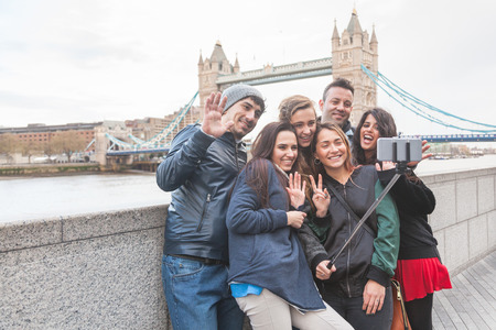 Group of friends taking a selfie using a selfie stick in London with Tower Bridge on background. They are four girls and two boys in their twenties, embracing and having fun together. Stock Photo