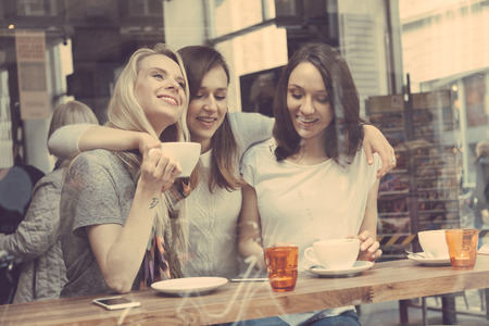 Happy women enjoying a coffee in a cafe in Copenhagen. They are in their twenties, laughing and talking each other. Smart casual clothing.