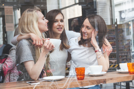 three friends: Happy women enjoying a coffee in a cafe in Copenhagen. They are in their twenties, laughing and talking each other. Smart casual clothing.