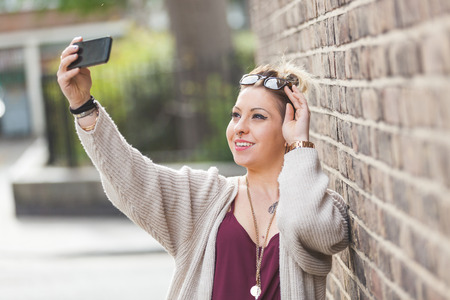 red cardigan: Hipster woman taking a selfie against a brick wall in London. Shes wearing high waisted shorts, a red top and a gray cardigan. She also wears eyeglasses and she has piercings and tattoos Stock Photo