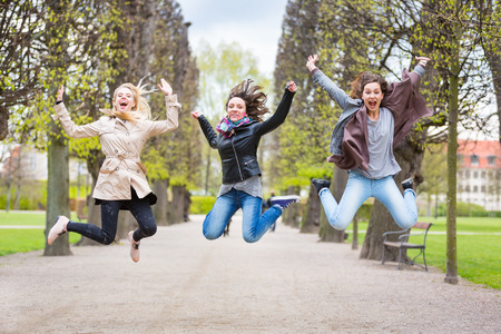 three persons only: Group of women jumping at park in Copenhagen. They are in their twenties and they are wearing smart casual clothes. Happiness, friendship and success concepts.