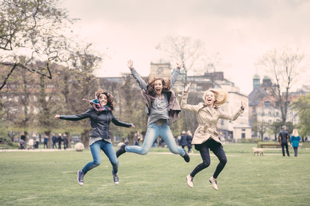denmark: Group of women jumping at park in Copenhagen. They are in their twenties and they are wearing smart casual clothes. Happiness, friendship and success concepts.
