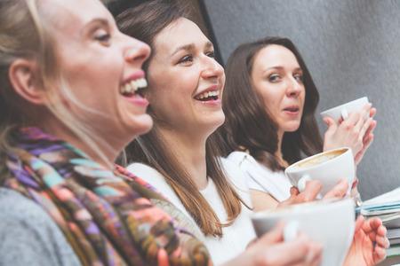 Gelukkig vrouwen genieten van een kopje koffie in een café in Kopenhagen. Ze zijn in de twintig, lachen en praten met elkaar. Smart casual kleding. Stockfoto