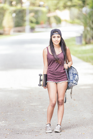 filipina: Beautiful girl walking at park holding a skateboard. She is half caucasian and half filipina, she wears short jeans, a purple tank top and a black cap. Stock Photo