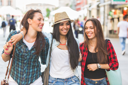 Three happy women walking in the city, talking each other and smiling. This is a mixed race group, one girl is half asian and one is middle eastern. Lifestyle, friendship and urban life concepts. photo