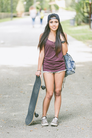 filipina: Portrait of a beautiful skater girl at park with her black skateboard. She is half caucasian and half filipina, she wears short jeans, a purple tank top and a black cap.