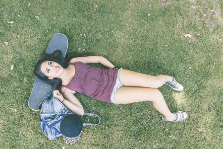 filipina: Beautiful skater girl relaxing at park, top view. She is lying on the grass with the head on the skate. She is half caucasian and half filipina, she wears short jeans and a purple tank top.
