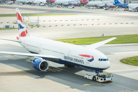 boeing: LONDON, UK - MAY 7, 2015: British Airways Boeing 777 at Gatwick LGW airport towed to runway by aircraft tug.