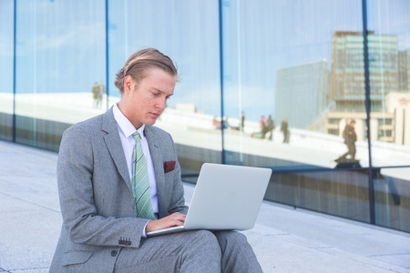 facial features: Fashioned young man working with laptop outdoor. He has nordic facial features, and wearing a light gray suit. There is a modern background with white stones and big windows.