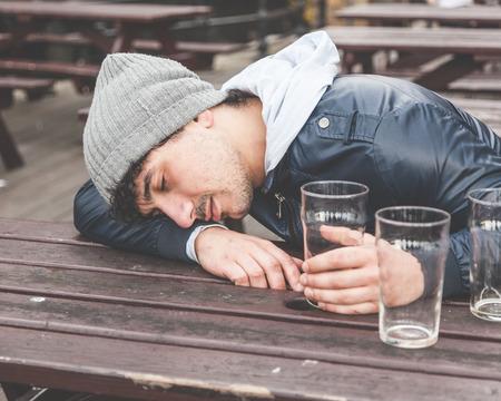 ロンドンのパブで寝て酔って若い男。彼はテーブルの上のいくつかの空のグラスと屋外のテーブルに座っています。
