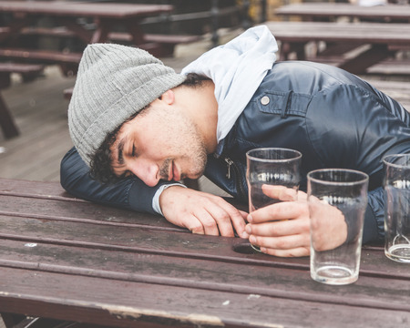 Drunk young man sleeping at pub in London. He is sitting at table outdoor with some empty glasses on the table.