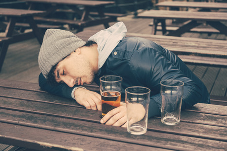 abusive: Drunk young man sleeping at pub in London. He is sitting at table outdoor with some empty glasses on the table.
