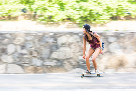 filipina: Beautiful mixed race girl skating in the city. She is half caucasian and half filipina, she wears short jeans, a purple tank top and a black cap. Side view with panning technique