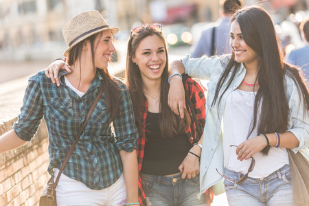 women friendship: Three happy women walking in the city, talking each other and smiling. This is a mixed race group, one girl is half asian and one is middle eastern. Lifestyle, friendship and urban life concepts.