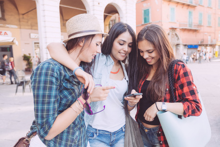 talking: Three young women with smart phone in the city, talking each other and smiling. This is a mixed race group, one girl is half asian and one is middle eastern. Lifestyle, friendship and urban life concepts.