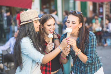 Three happy women eating ice cream in the city, talking each other and smiling. This is a mixed race group, one girl is half asian and one is middle eastern. Lifestyle, friendship and urban life concepts. Imagens