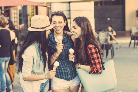 eating ice cream: Three happy women eating ice cream in the city, talking each other and smiling. This is a mixed race group, one girl is half asian and one is middle eastern. Lifestyle, friendship and urban life concepts. Stock Photo
