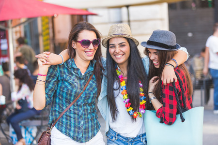 middle eastern clothing: Three happy young women in the city, talking each other and smiling. This is a mixed race group, one girl is half asian and one is middle eastern. Lifestyle, friendship and urban life concepts.