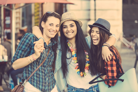 middle eastern woman: Three happy young women in the city, talking each other and smiling. This is a mixed race group, one girl is half asian and one is middle eastern. Lifestyle, friendship and urban life concepts.