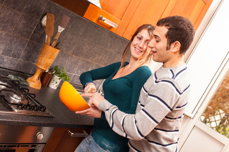 desayuno romantico: Hombre que intenta probar algo en la cocina Foto de archivo