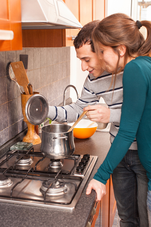 Wife and Husband Cooking Together in the Kitchen photo
