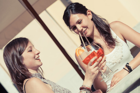 Two Young Women Cheering with Cold Drinks Stock Photo