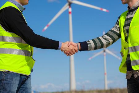 turbine: Engineers giving Handshake in a Wind Turbine Power Station Stock Photo